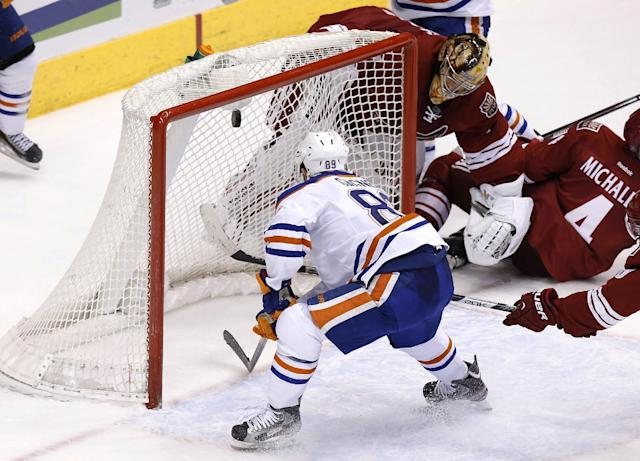 Edmonton Oilers' Sam Gagner (89) scores a goal as Phoenix Coyotes' Thomas Greiss, of Germany, top right, is caught behind the net during the third period of an NHL hockey game, Friday, April 4, 2014, in Glendale, Ariz. The Oilers defeated the Coyotes in a shootout, 3-2. (AP Photo/Ross D. Franklin)