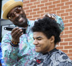 """In this photo provided by Gregg Gelmis, barber Jeff Johnson, left, cuts 17-year-old Kieran Moïse's hair, which was then donated to the nonprofit Children with Hair Loss, Saturday, May 29, 2021, in Huntsville, Ala. Moïse also launched a fundraiser through St. Jude Children's Research Hospital in memory of classmate Josh Quist, who died from cancer. So far their charity, """"Kieran's Curls for Cancer,"""" has raised $35,000. (Courtesy of Gregg Gelmis via AP)"""
