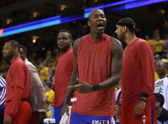 Los Angeles Clippers' Jamal Crawford, second from right, argues with a fan during the second half in Game 4 of an opening-round NBA basketball playoff series against the Golden State Warriors on Sunday, April 27, 2014, in Oakland, Calif. Clippers players wore their warmups inside out in protest of team owner Donald Sterling's alleged racial remarks. Golden State won 118-97. (AP Photo/Marcio Jose Sanchez)