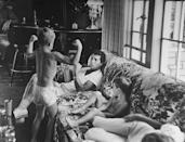<p>Dean Martin's son flexes his muscles while the singer relaxes with his family at home in 1958. </p>