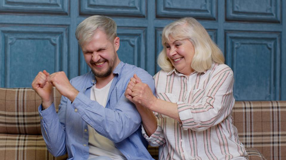 Smiling young man with gray-haired old mom or grandmother dancing, laughing. Good friends. Happy bonding loving generations family of senior mother and handsome adult son or grandson moving in dance