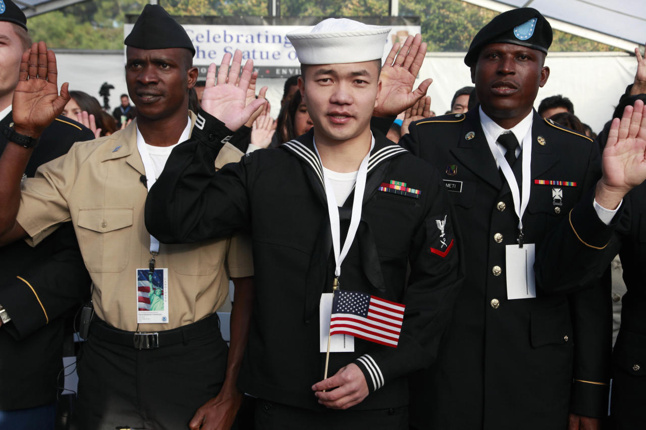 Zuyu Nu, center, from China and serving with the U.S. Navy, takes the oath of citizenship during a naturalization ceremony at the Statue of Liberty, Friday, Oct. 28, 2011in New York. The oath of citizenship was taken by 125 people, to mark the Statues's 125th anniversary. On the left is Adeniyi Ismail Rufai from Nigeria and serving with the Navy, and on the right is Patrick Kudzo Azameti from Ghana and serving the U.S. Army. (AP Photo/Mark Lennihan)