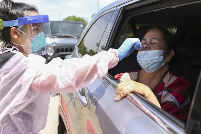 Nurse Ruby Lewis (from left) administers a covid-19 test to Laling Riklon of Springdale, Ark. at the Center for Nonprofits parking lot in Springdale, Ark., Saturday, May 23, 2020. The Arkansas Department of Health partnered with the Arkansas Coalition of Marshallese to host a drive-thru covid-19 testing site. Volunteers also distributed groceries and masks to those waiting in line. (NWA Democrat-Gazette/Charlie Kaijo)