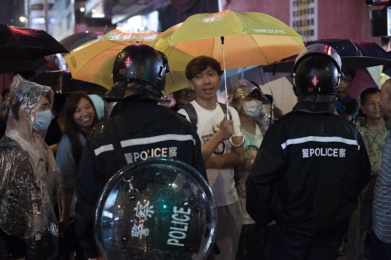 Pro-democracy protesters stand their ground in front of riot police in the Mong Kok district of Hong Kong on October 22, 2014 (AFP Photo/Nicolas Asfouri)
