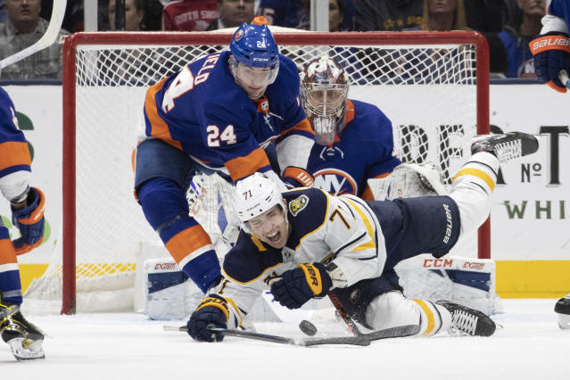 New York Islanders defenseman Scott Mayfield (24) holds down Buffalo Sabres left wing Evan Rodrigues (71) in the second period of an NHL hockey game, Saturday, Dec. 14, 2019 in Uniondale, N.Y. (AP Photo/Mark Lennihan)