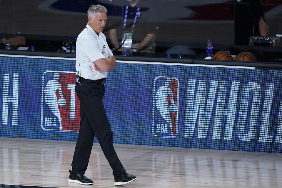 Brett Brown walks on the sideline during a game.
