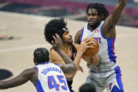 Cleveland Cavaliers' Jarrett Allen, center, drives to the basket against Detroit Pistons' Isaiah Stewart and Detroit Pistons' Sekou Doumbouya, left, in the first half of an NBA basketball game, Wednesday, Jan. 27, 2021, in Cleveland. (AP Photo/Tony Dejak)