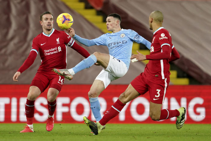 Manchester City's Phil Foden controls the ball between Liverpool's Jordan Henderson, left, and Liverpool's Fabinho during the English Premier League soccer match between Liverpool and Manchester City at Anfield Stadium, Liverpool, England, Sunday, Feb. 7, 2021. (AP photo/Jon Super, Pool)
