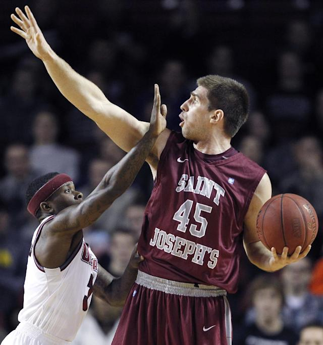 Massachusetts guard Chaz Williams, left, reaches up as he tries to block the view of Saint Joseph's forward Tyler Bergantino during the first half of an NCAA college basketball game in Amherst, Mass., Wednesday, Jan. 8, 2014. (AP Photo/Charles Krupa)