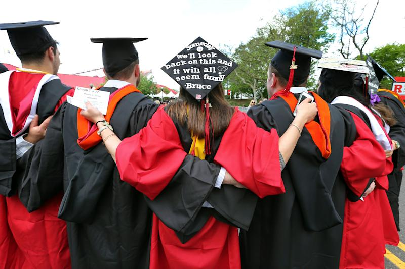 FILE - In this May 15, 2016 file photo, students embrace as they arrive for the Rutgers graduation ceremonies in Piscataway, N.J. More Americans are getting buried by student debt, causing delays in home ownership, limiting how much people can save and leaving taxpayers at risk as many loans go unpaid. (AP Photo/Mel Evans)