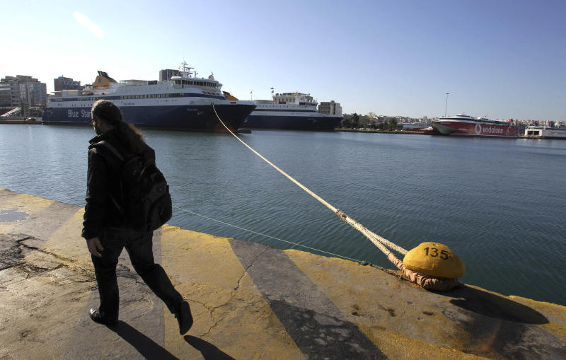 A man passes a moored ferry during a 24-hour nationwide strike by Greek seamen's union in the port of Piraeus, near Athens, Tuesday, April 16, 2013. The union called the strike on Tuesday to protest labor reforms that unions say will undermine their collective bargaining rights. The new draft bill is due to be debated in Parliament on the day of the strike. (AP Photo/Thanassis Stavrakis)