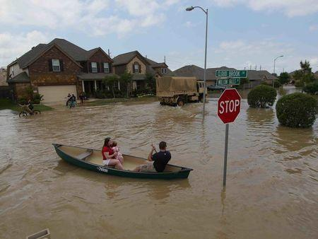 A woman holds a baby in a canoe as Texas Guardsmen arrive to assist after flooding in Brookshire, Texas, U.S. April 20, 2016. U.S. Army National Guard/1st Lt. Zachary West/Handout via REUTERS