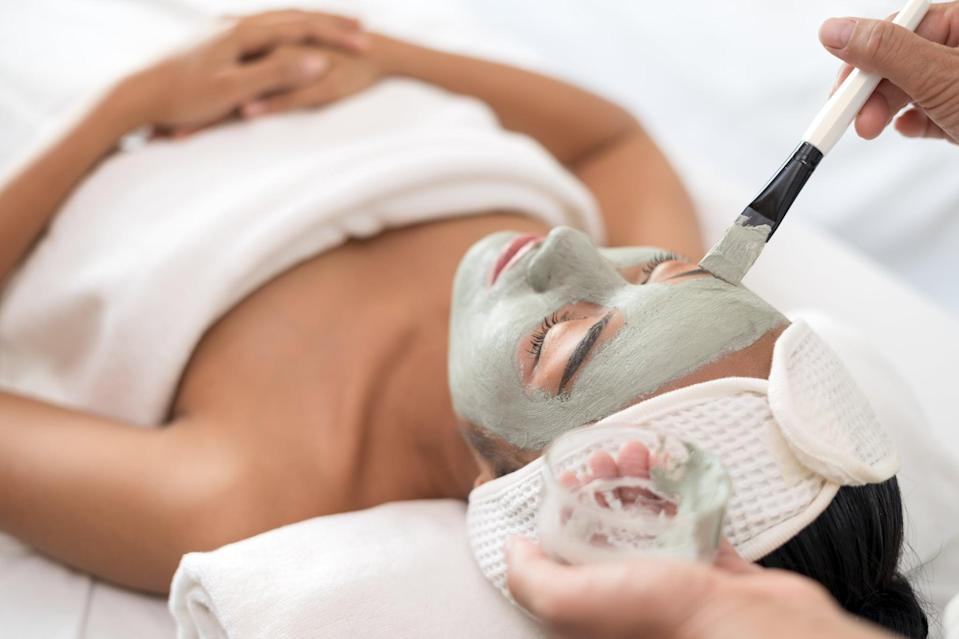 Close up of beautician applying clay mask on woman's face during beauty treatment in spa