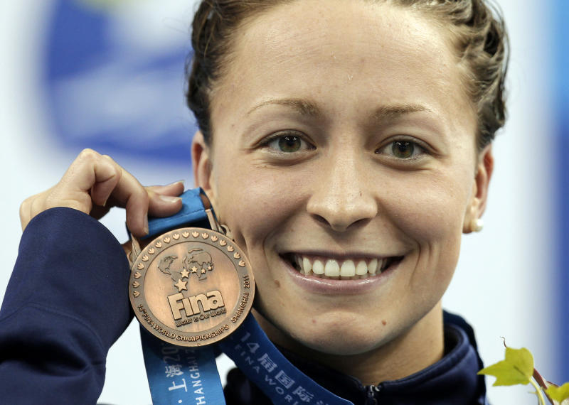 FILE - In this July 25, 2011, file photo, Ariana Kukors, of the United States, holds her bronze medal for the women's 200-meter Individual Medley final at the FINA 2011 Swimming World Championships in Shanghai, China. The U.S. Olympic champion swimmer has accused a team coach of sexually abusing her starting when she was 16, the latest misconduct allegations against those charged with caring for young athletes. Ariana Kukors, now 28, told authorities that Sean Hutchison sexually abused her as a minor and took thousands of sexually explicit photographs of her. (AP Photo/Michael Sohn, File)
