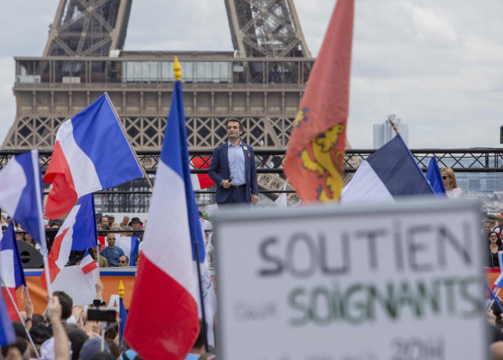 Head of right-wing party 'Les Patriotes' Floriant Philippot stands in front of thousands of protesters gathered at Place Trocadero near the Eiffel Tower attend a demonstration in Paris, France, Saturday July 24, 2021, against the COVID-19 pass which grants vaccinated individuals greater ease of access to venues. (AP Photo/Rafael Yaghobzadeh)