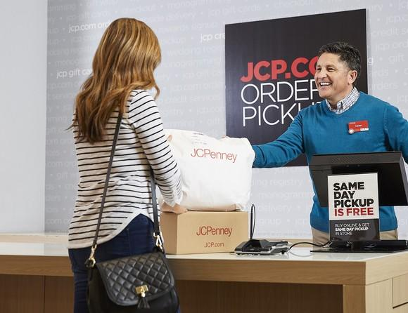 Person picking up packages from clerk behind counter with sign reading JCP.com Order Pickup.