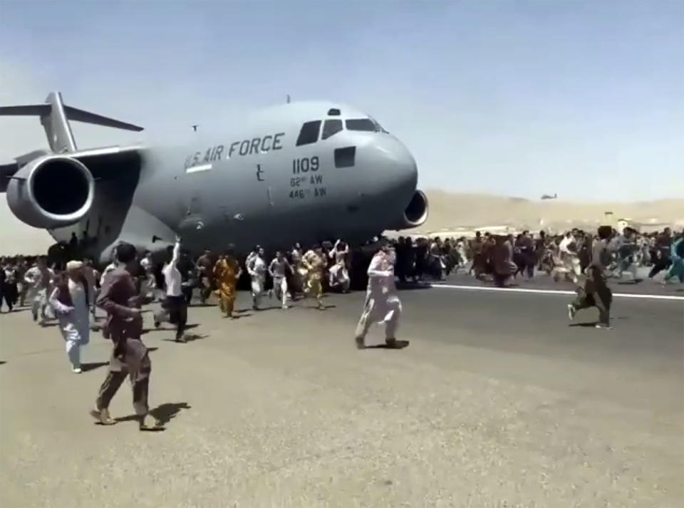 FILE - In this Aug. 16, 2021 file photo, hundreds of people run alongside a U.S. Air Force C-17 transport plane as it moves down a runway of the international airport, in Kabul, Afghanistan. Twin tragedies on opposite sides of the world are piling misery on people that have seen far more than their share. In Afghanistan, a group of gunmen known for sadistic tyranny rocketed back into power after 20 years as Western and Afghan leaders walked away with a sad shrug. (AP Photo)