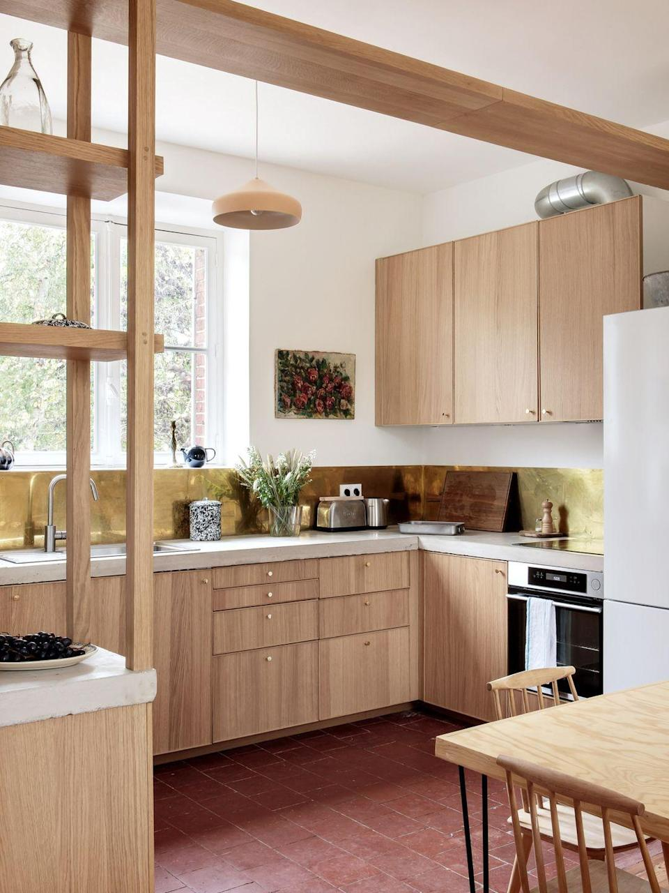 "<p>Bespoke wood fronts on the IKEA cabinets and a slim brass backsplash elevate the kitchen at <a href=""https://www.riversidehousenormandy.com/"" rel=""nofollow noopener"" target=""_blank"" data-ylk=""slk:Riverside House"" class=""link rapid-noclick-resp"">Riverside House</a> in Normandy to new heights. Thoughtful details—tiny metallic knobs, open shelves that match the cabinetry—give the whole room a custom look. </p>"