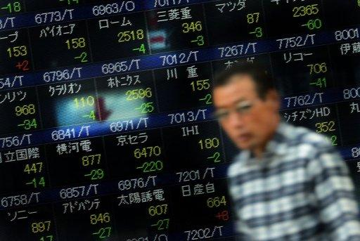 A man walks past a board displaying share prices for the Tokyo Stock Exchange in Tokyo in October 2012