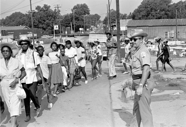 <p>Neshoba County Deputy Sheriff Cecil Price watches marchers as they pass through Philadelphia, Miss., during a memorial for three slain civil rights workers, June 21, 1965. Price is charged with conspiracy to violate the civil rights of the three Freedom Summer activists slain by Klansmen in 1964. Seven Ku Klux Klansmen were convicted of federal civil rights violations in the deaths and sentenced to prison terms ranging from three to ten years; none served more than six years. (Photo: Jack Thornell/AP) </p>