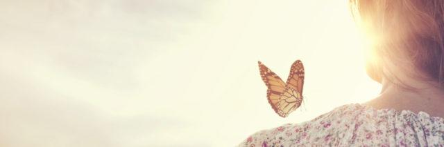 a woman looking into the distance with a butterfly near her shoulder