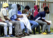 Without practicing social distancing, people queue outside home affairs offices for document in Port Elizabeth, South Africa, Friday, Nov. 13, 2020. The Eastern Cape Province is seeing a surge in cases of coronavirus and has recorded the highest number of COVID-19-related deaths in the country. (AP Photo/Theo Jeptha)