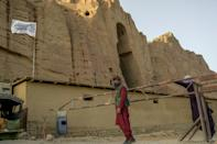 The Taliban fly their flag at the site where a Buddha statue once stood, before it was destroyed by the militants' former regime (AFP/BULENT KILIC)