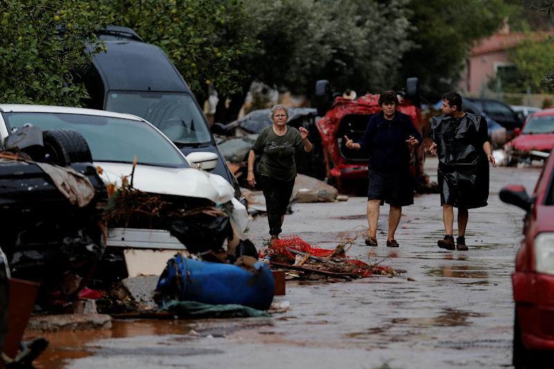 Locals walk next to destroyed cars following heavy rainfall.