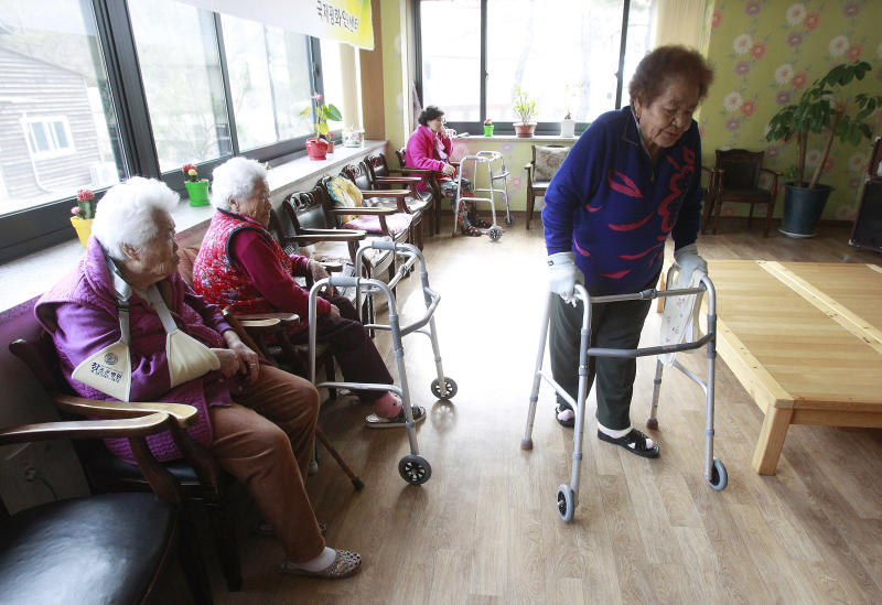 Kim Gun-ja, 89, right, former comfort woman who was forced to serve for the Japanese troops as a sexual slave during World War II, passes by other comfort woman Yi Ok-seon, 88, left, and Kim Wei-han, 86, at the House of Sharing, a nursing home and museum for 10 former sex slaves, in Toechon, South Korea. There are only 55 women left who registered with the South Korean government as former sex slaves from the war _ down from a peak of more than 230. Their average age is 88. (AP Photo/Ahn Young-joon)