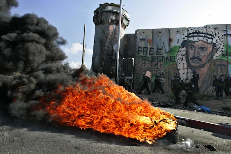 """Israeli soldiers run past burning tires under a mural of the late Palestinian leader Yasser Arafat during clashes with Palestinian stone throwers following a protest to mark the upcoming 63rd anniversary of """"Nakba"""", Arabic for """"Catastrophe"""", the term used to mark the events leading to Israel's founding in 1948, in the Qalandia checkpoint between Ramallah and Jerusalem, Saturday, May 14, 2011.(AP Photo/Majdi Mohammed)"""