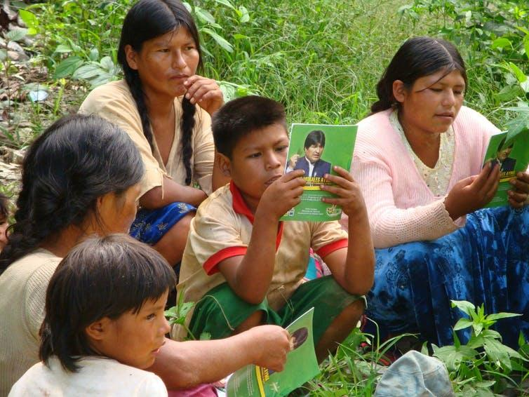 Three women and two children read green leaflets.