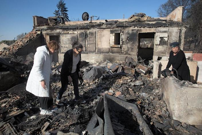 Israeli settlers inspect their burnt houses in the Halamish settlement, also known as Neveh Tzuf, in the occupied West Bank on November 27, 2016, after 45 homes were damaged or completely destroyed by fire (AFP Photo/Menahem Kahana)
