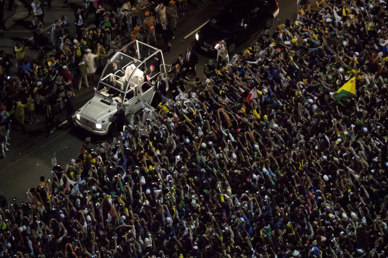 FILE -- In this file photo taken on the Copacabana beachfront in Rio de Janeiro, Brazil, on July 25, 2013, Pope Francis greets from his popemobile as he makes his way through the crowds. Francis' flouting of rules has extended to saints (he's declared three of them without going through the Vatican's miracle-confirmation protocol) and to security: He ditched the armored popemobile for his first foreign trip to Brazil, and promptly got swarmed by adoring crowds in Rio when his motorcade took a wrong turn. (AP Photo/Felipe Dana)