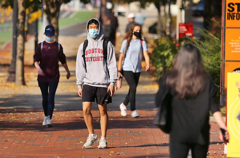 BOSTON, MA - OCTOBER 22: BU students walk down Commonwealth Ave. outside the George Sherman Union (GSU) at Boston University in Boston on Oct. 22, 2020. Starting Thursday, BU students will be required to show a green badge on their phones showing that they had tested negative for Covid-19 before they enter dining areas. (Photo by John Tlumacki/The Boston Globe via Getty Images)
