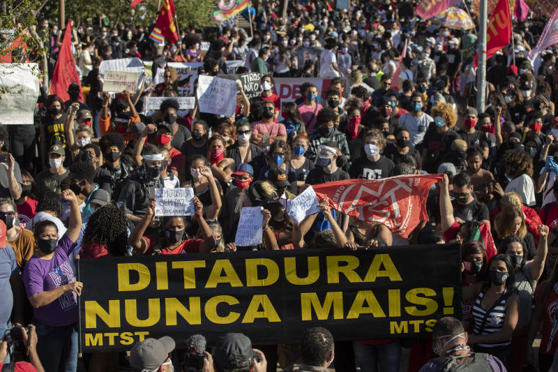 """Demonstrators holding a banner that reads in Portuguese """"Dictatorship never more"""" protest against racism and Brazilian president Jair Bolsonaroand in Sao Paulo, Brazil, Sunday, June 7, 2020. (AP Photo/Andre Penner)"""