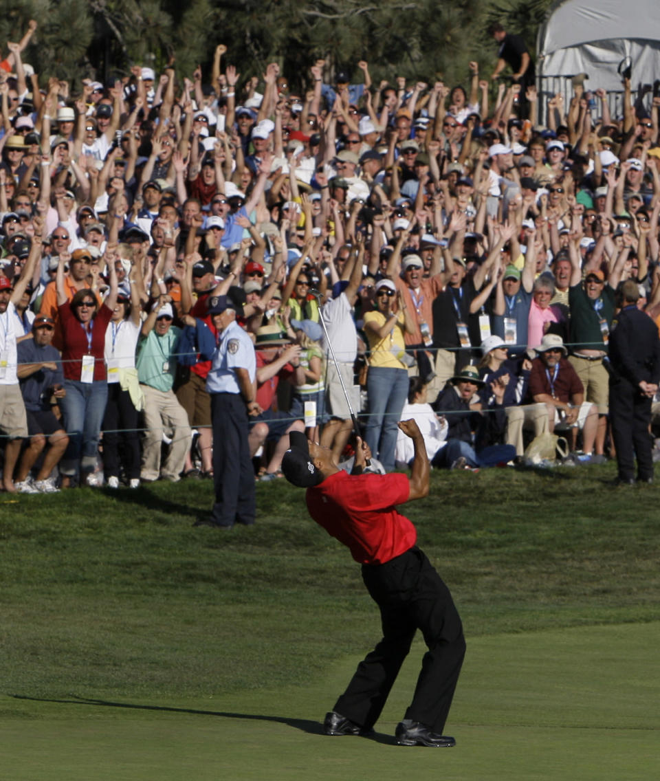 FILE - In this June 15, 2008, file photo, Tiger Woods reacts after sinking a birdie putt on the 18th green, forcing a playoff against Rocco Mediate during the fourth round of the U.S. Open golf tournament at Torrey Pines Golf Course in San Diego. The U.S. Open returns to Torrey Pines on June 17-20, minus Woods as he recovers from leg injuries in a car crash. (AP Photo/Chris Carlson, File)