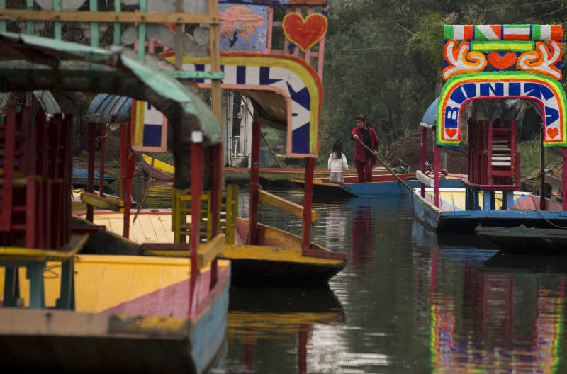 A woman takes a young girl to school by boat, in Xochimilco, on the southern edge of Mexico City, Wednesday, May 7, 2014. In Xochimilco, busy markets stand side by side with colonial churches, and children ride to school in boats pushed by poles, along a network of canals and floating gardens that date to pre-hispanic times. The popular tourist destination was declared a UNESCO world heritage site in 1987.(AP Photo/Rebecca Blackwell)