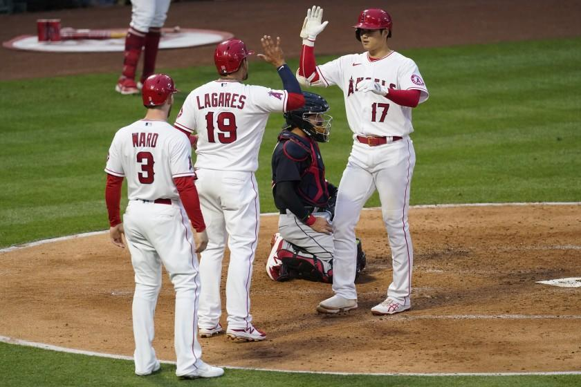 Los Angeles Angels designated hitter Shohei Ohtani (17) celebrates with Taylor Ward (3) and Juan Lagares (19) after hitting a home run during the second inning of a baseball game against the Cleveland Indians Monday, May 17, 2021, in Los Angeles. All three scored. (AP Photo/Ashley Landis)