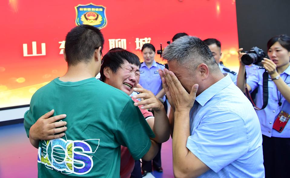 Guo Gangtang, 51, and his wife reunite with their son Guo Xinzhen, who was abducted 24 years ago at the age of 2, at a family reunion arranged by the police, in Liaocheng, Shandong province, China July 11, 2021. Picture taken July 11, 2021. China Daily via REUTERS  ATTENTION EDITORS - THIS IMAGE WAS PROVIDED BY A THIRD PARTY. CHINA OUT.