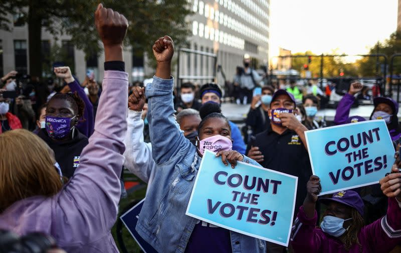 People react while holding signs after Election Day in Washington