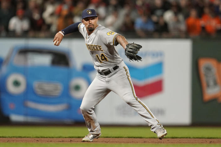 Milwaukee Brewers third baseman Jace Peterson (14) throws out San Francisco Giants' Wilmer Flores at first base during the sixth inning of a baseball game in San Francisco, Monday, Aug. 30, 2021. (AP Photo/Jeff Chiu)