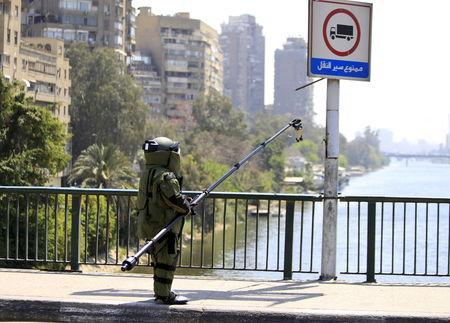 A bomb detonation expert in his suit, accompanied by security personnel (obscured), checks the area after a bomb exploded on a bridge in the Cairo district of Zamalek, April 5, 2015. REUTERS/Mohamed Abd El Ghany