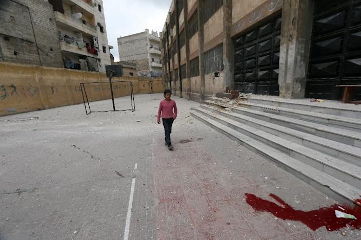 A Syrian child walks past a pool of blood at the entrance of the Saad Ansari school in the northern city of Aleppo on April 12, 2015, following a reported Syrian regime air strike that killed five children and four other civilians (AFP Photo/Zein Al-Rifai)