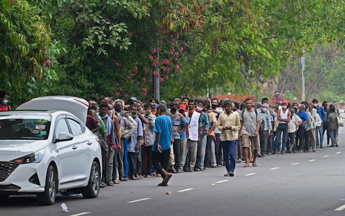 Homeless people mostly working as daily wage labourers and are out of jobs due to the lockdown queue as volunteers distribute food along the roadside - Prakash SINGH / AFP