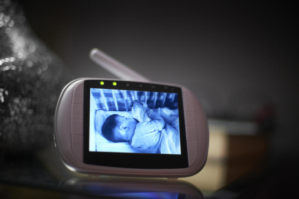 Baby monitor on bedside table in the bedroom with the image of the baby sleeping on the screen