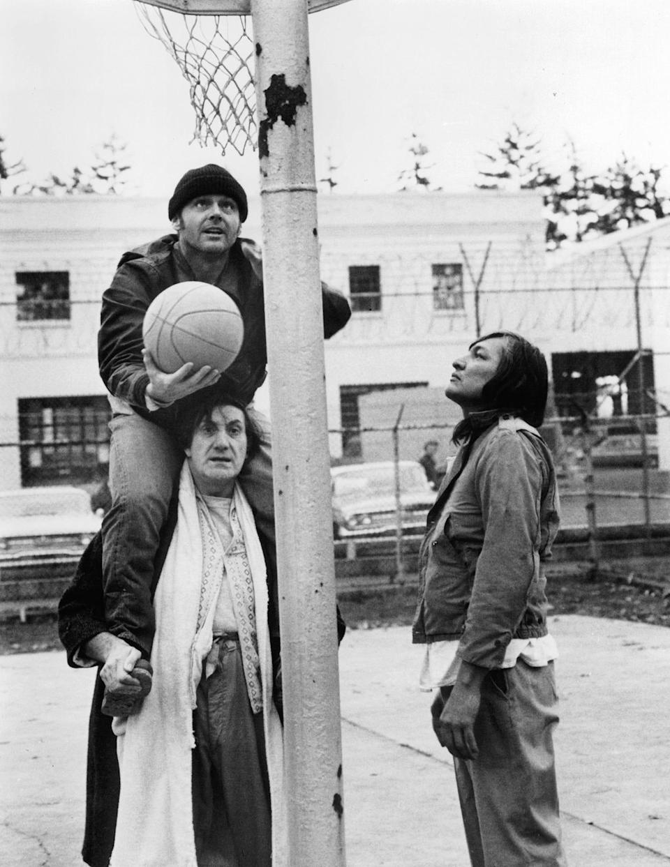 Jack Nicholson shooting basket on the shoulders of Josip Elic as Will Sampson watches in a scene from the film 'One Flew Over The Cuckoo's Nest', 1975.