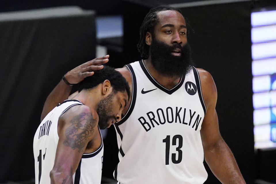 Brooklyn Nets guard Kyrie Irving, left, gets a pat on the head from guard James Harden during a timeout in the first half of the team's NBA basketball game against the Los Angeles Clippers on Sunday, Feb. 21, 2021, in Los Angeles. (AP Photo/Mark J. Terrill)