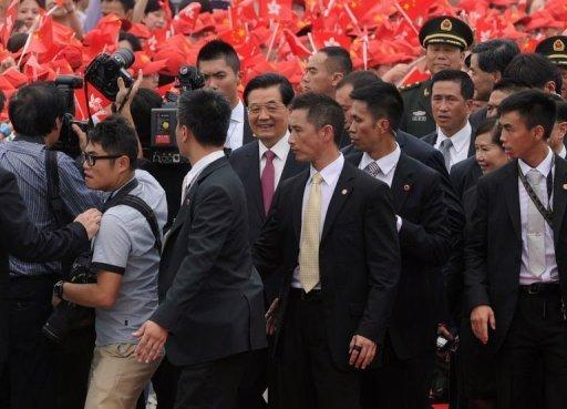Chinese President Hu Jintao (centre) smiles after arriving at Hong Kong's International airport