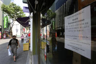 A notice is seen at the entrance of a temporarily closed store at a shopping district in Seoul, South Korea, Sunday, Aug. 23, 2020. South Korea has added nearly 400 new coronavirus cases, counting its tenth straight day of triple-digit increases as the speed of viral spread nears the levels the country saw during the worst of its outbreak in spring. (AP Photo/Ahn Young-joon)