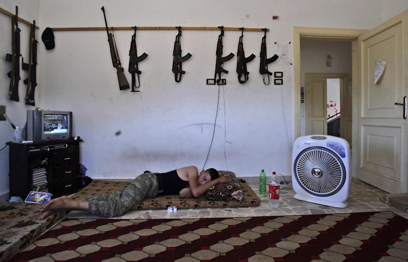 In this Sunday, Aug. 26, 2012 photo, a Syrian rebel sleeps after returning back from fighting government forces in Aleppo, at a rebel headquarters in Marea on the outskirts of Aleppo, Syria. Rebels have taken a major stride in uniting their ranks in the battle for Syria's largest city, giving them hope they could tip the balance in three-months of bloody stalemate in Aleppo, one of the biggest prizes of the civil war.. The question is how much more destruction the city can bear. Regime troops are retaliating with heavier bombardment, and civilians are bearing the brunt, their neighborhoods left in rubble. (AP Photo/Muhammed Muheisen)